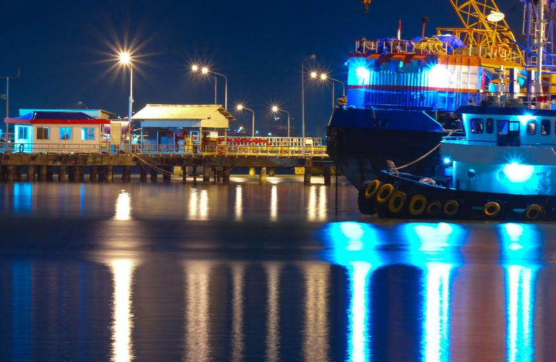 Illuminated boats moored at harbor against sky at night