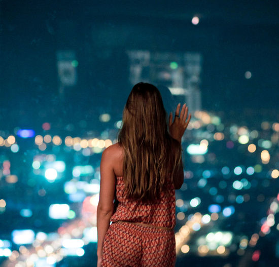 Woman standing back and watching the city at night through the stained-glass window Night Rear View Real People Standing Illuminated Focus On Foreground Lifestyles One Person Women Leisure Activity Adult Long Hair Three Quarter Length Waist Up City Hair Hairstyle Young Adult Architecture Outdoors Nightlife