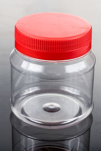 Plastic jar bottle container with red cover lid against dark background Plastic Bottle Bottle Cap Close-up Container Empty Gray High Angle View Indoors  Lid No People Plastic Red Single Object Still Life Studio Shot