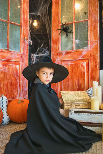 Portrait of boy wearing witch costume at home