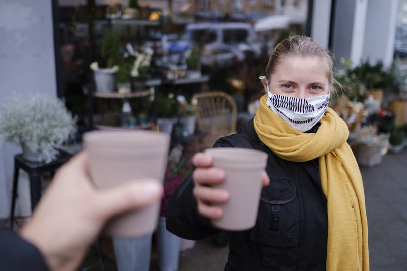 Portrait of woman wearing mask holding coffee cup while standing outdoors