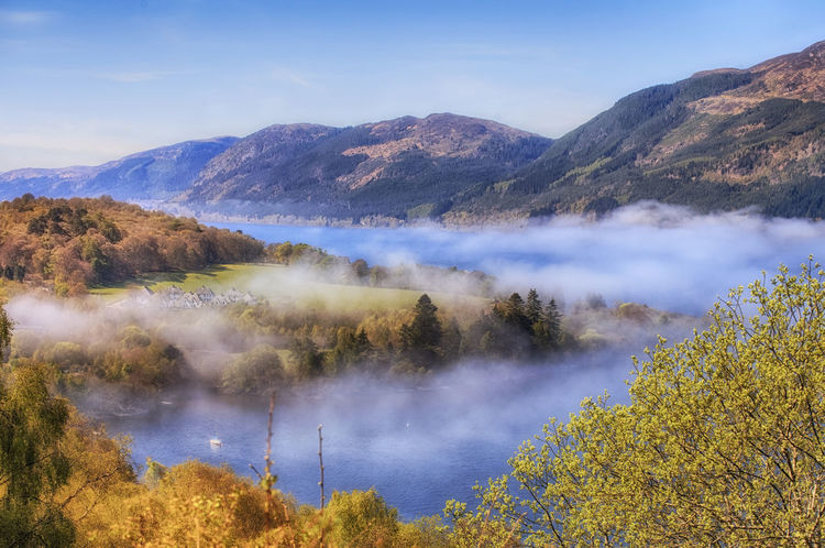View from the hill to Loch Ness lake with white morning fog over water, Scotland, UK Beauty In Nature Blue Day Fog Over Water Forest Lake Landscape Loch  Loch Ness Lochness Morning Mountain Mountain Range Natural Parkland Nature Ness No People Outdoors Reflection Scenics Scotland Sky Sunset Uk Water