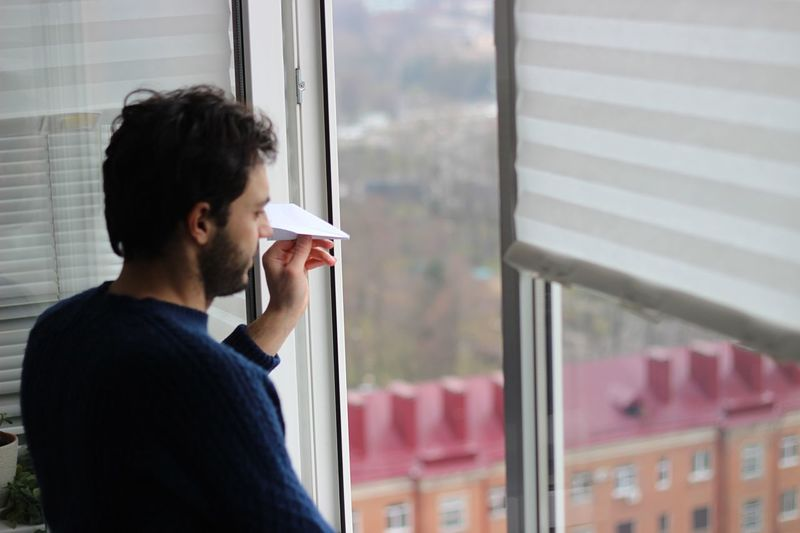 High Angle View Of Man Holding Paper Airplane While Standing By Window At Home