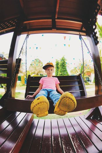 Boys Casual Clothing Child Childhood Day Front View Full Length Innocence Leisure Activity Lifestyles Looking At Camera Males  Men One Person Outdoor Play Equipment Outdoors Portrait Real People Sitting