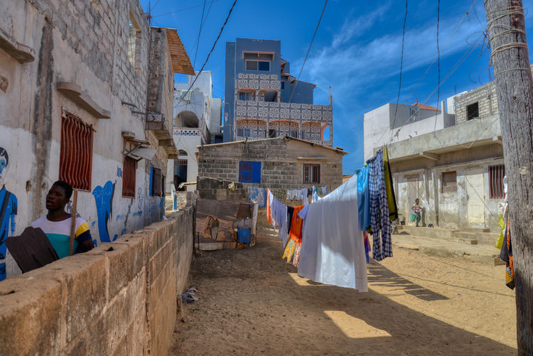 Clothes drying on street amidst buildings in city