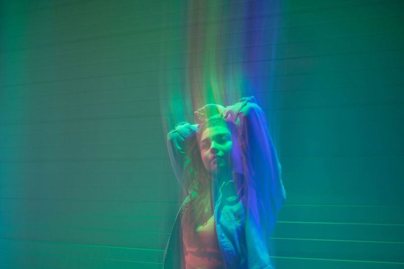 Digital composite image of woman with hand in hair and illuminated against wall