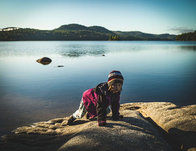 Girl standing on rock by lake against sky