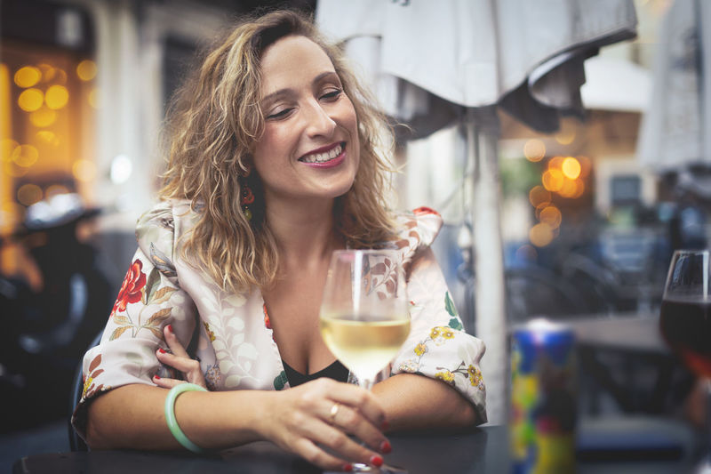 Smiling Woman Having Wine While Sitting At Table In Restaurant