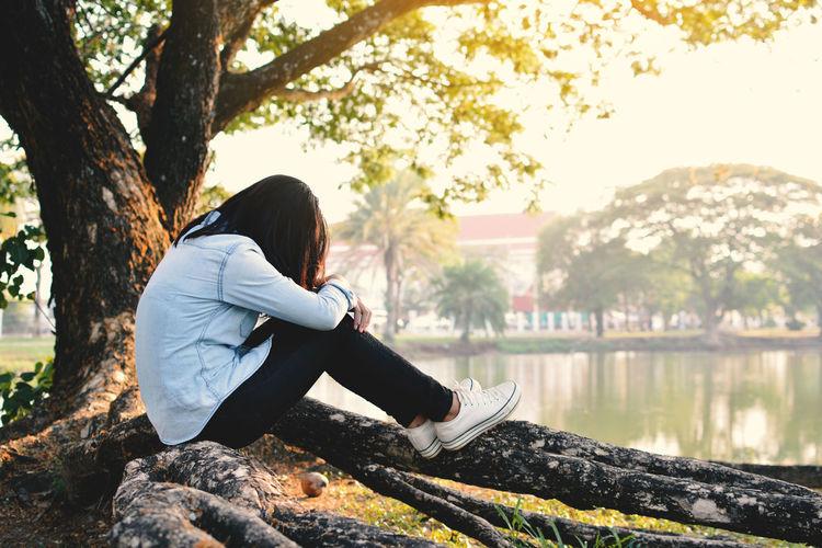Woman Sitting On Fallen Tree By Lake
