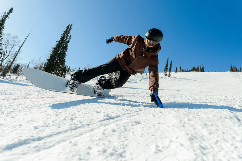 Rear view of man skiing on snow against sky