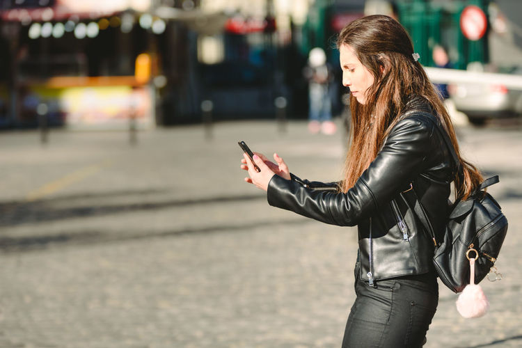 Side view of woman using smart phone on street