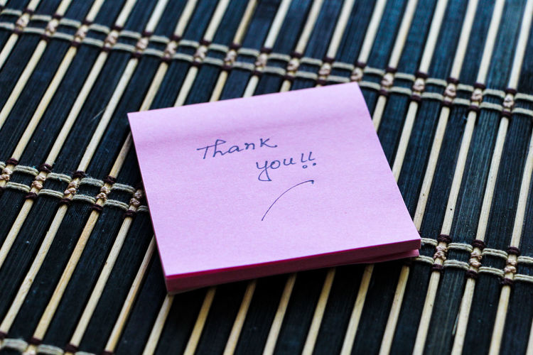 High angle view of thank you text on adhesive note