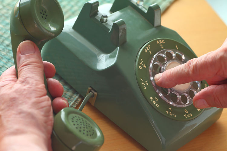 Cropped Hand Of Person Dialing Vintage Landline Phone