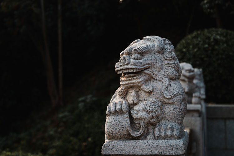 Close-up of stone lion statue against trees
