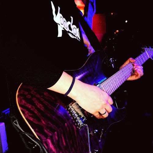 Low section of person playing guitar