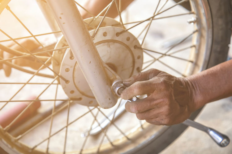 Close-up of man working with bicycle
