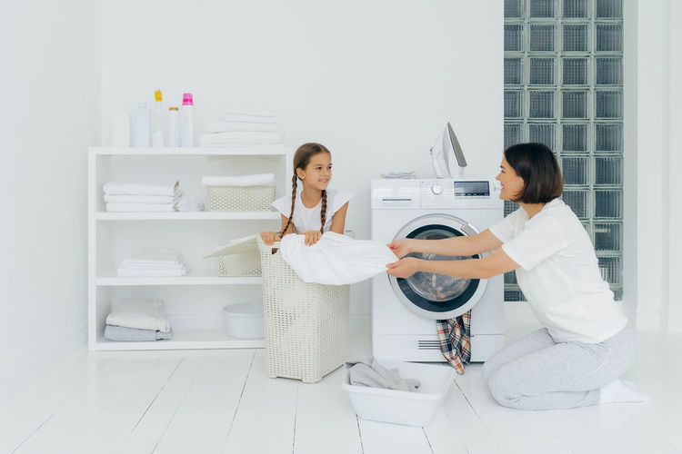 Mother and daughter putting laundry in washing machine at home