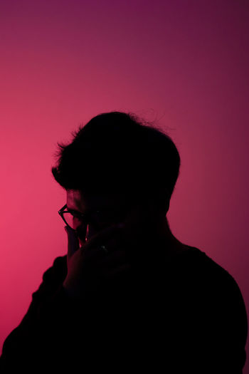 Portrait of silhouette man standing against pink background