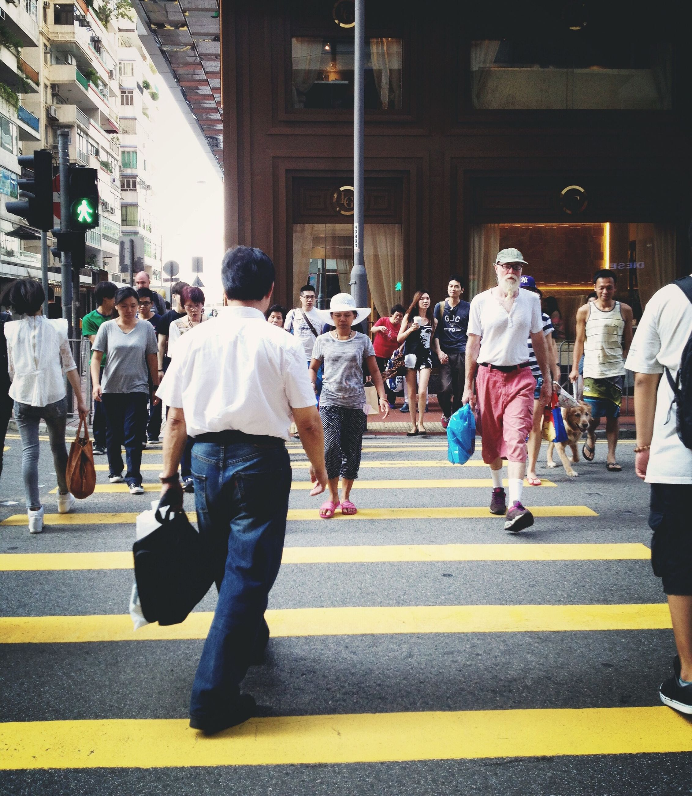 men, large group of people, person, walking, lifestyles, street, city life, city, leisure activity, full length, built structure, architecture, rear view, casual clothing, medium group of people, transportation, building exterior, on the move, group of people