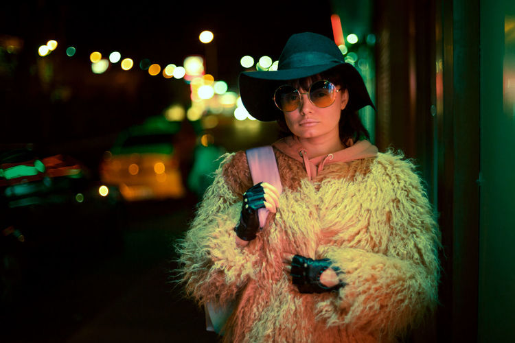 Woman wearing hat while standing outdoors at night