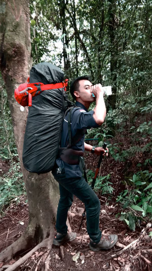 Full length of man holding camera while standing by tree in forest
