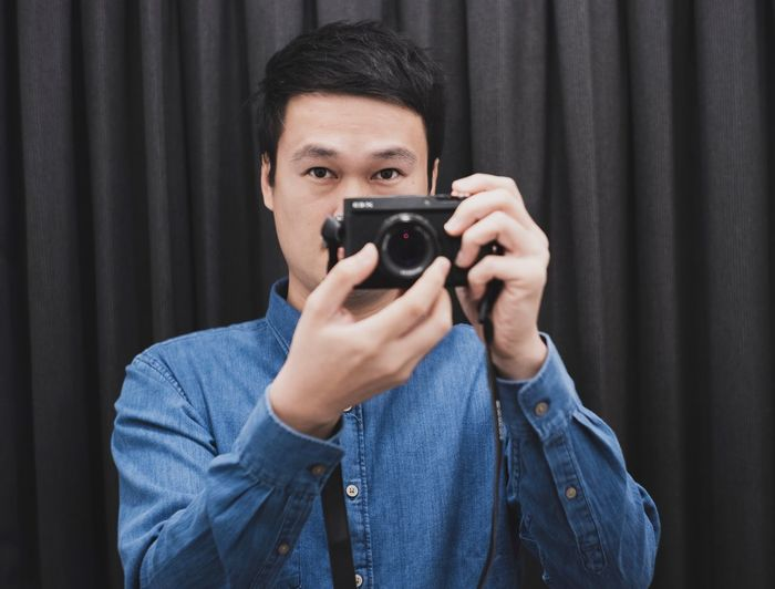 a man taking photography Photography Themes Camera - Photographic Equipment Photographing Technology One Person Portrait Holding Activity Photographic Equipment Real People Camera Men Photographer Indoors  Looking At Camera Front View