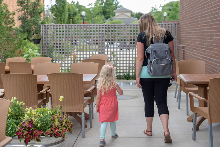 Rear view of mother with daughter walking at outdoor cafe