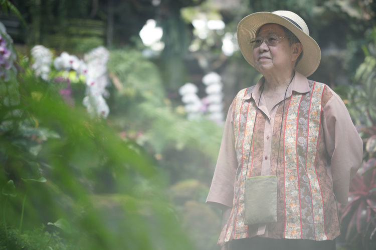 Woman wearing hat standing against plants