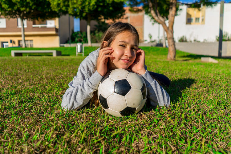 Portrait of smiling girl with ball on grass