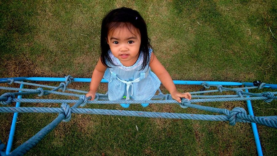 Portrait of cute girl climbing on rope in playground