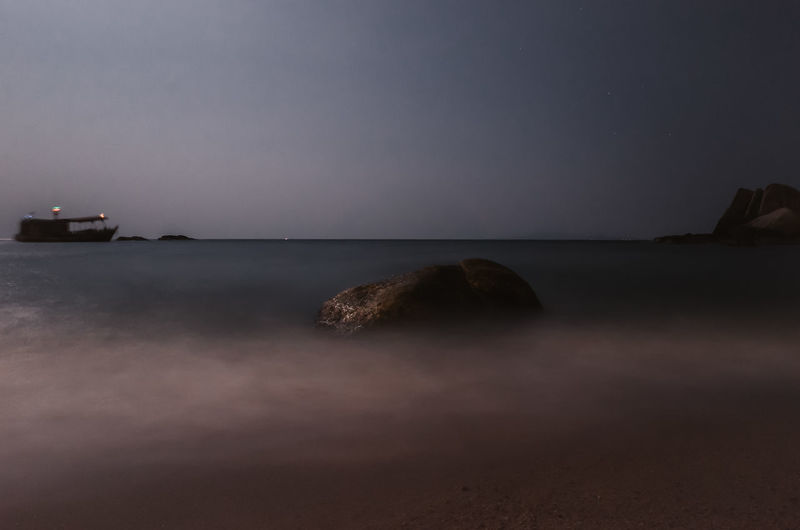 long exposure of a ship and a two rocks in the sea at Koh Tao Island, Thailand Sky Water Scenics - Nature Sea Tranquility Beauty In Nature Tranquil Scene Horizon Over Water Long Exposure Horizon Nature Land No People Beach Rock Idyllic Night Motion Dusk Boat Fishing Net Fishing Boat Thailand ASIA Ocean Tranquility