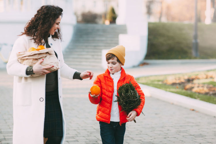 A beautiful mother with her son in a bright orange jacket and a fashionable yellow hat are walking