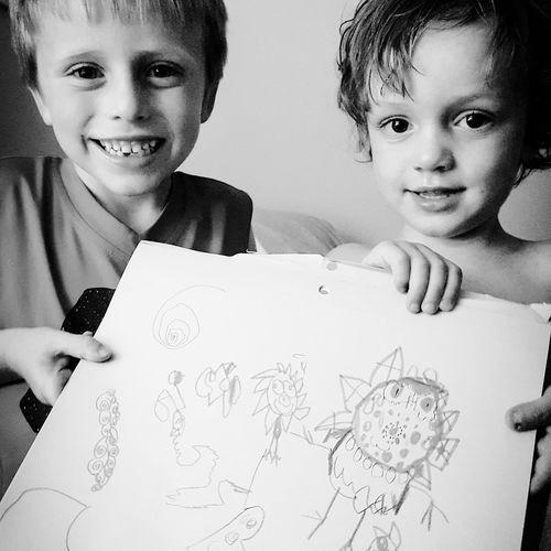 Portrait of siblings holding drawing at home