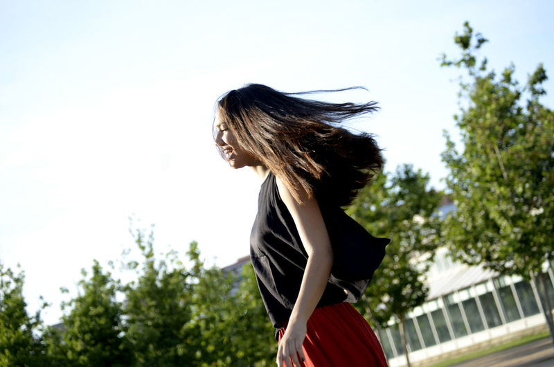 Side view of happy teenage girl tossing hair against sky