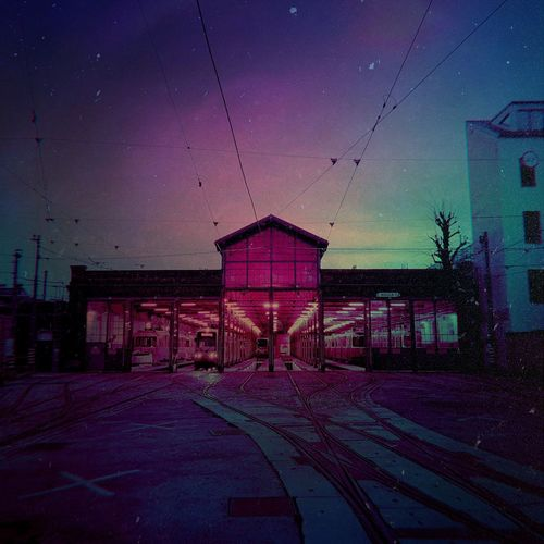 Illuminated railroad station by building against sky at dusk
