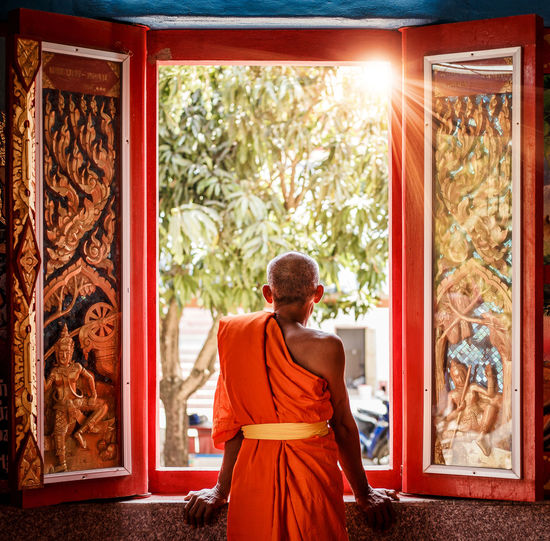 Rear View Of Monk Looking Through Window At Temple