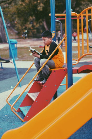 Boy reading book while sitting on outdoor play equipment at park
