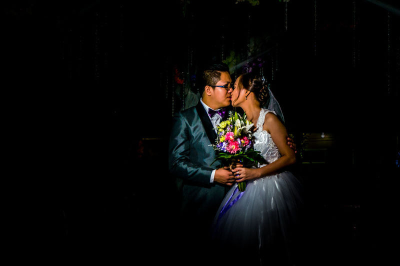 Newlywed couple kissing while standing against black background