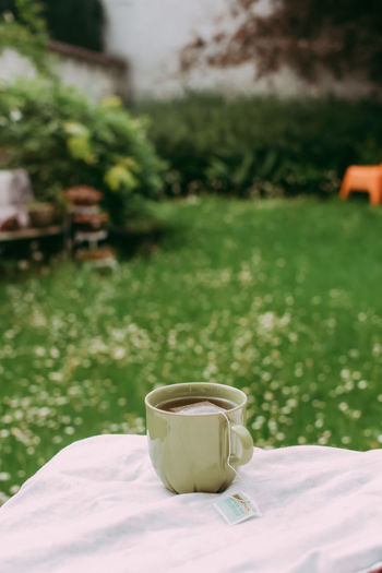 Coffee cup on table in field
