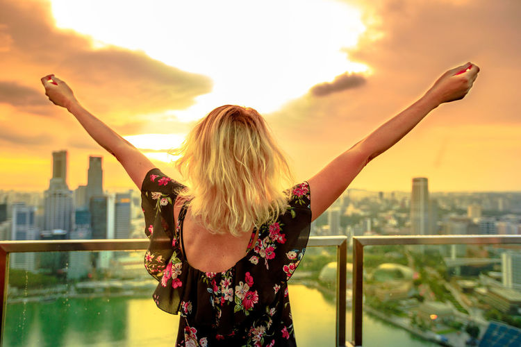 Carefree blonde woman looking panorama from rooftop in South Marina, Singapore. Aerial view of cityscape skyline at sunset. Lifestyle tourist at observation deck above financial district skyscrapers. Singapore Singapore City Woman Tourist Tourist Attraction  Tourist Destination People Girl Females Aerial View Skyline Cityscape Panorama Happy Travel Hat Lifestyle Enjoy Nature Tourism Sky One Person Railing Real People Standing Women Lifestyles Sunset Rear View Hair Architecture Leisure Activity Built Structure Human Arm Building Exterior City Focus On Foreground Blond Hair Hairstyle Outdoors Arms Raised Looking At View
