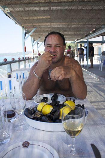 Shirtless man eating seafood at restaurant