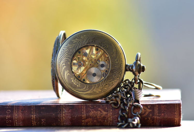 Close-Up Of Pocket Watch On Book During Sunny Day