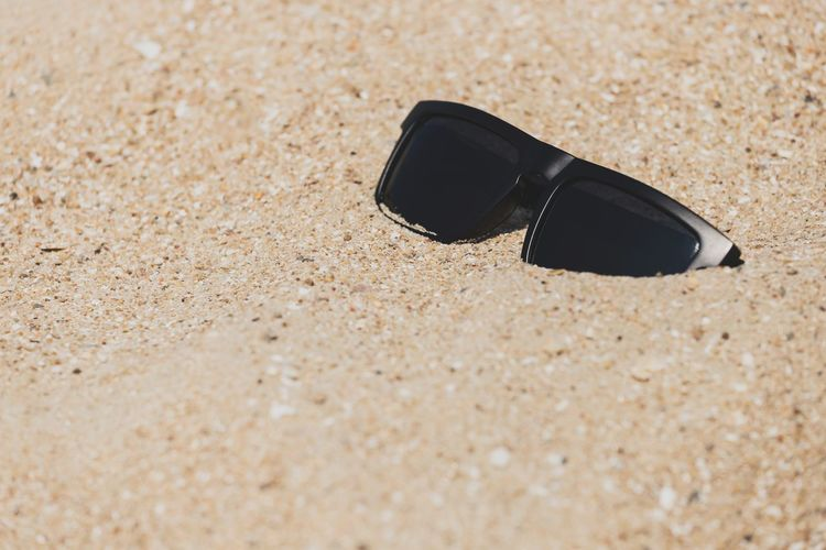 High angle view of sunglasses on sand