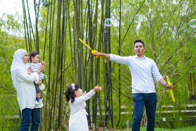 Playful family spending time together at park. Group Of People Men Standing Togetherness Three Quarter Length Plant Adult Smiling Human Body Part Women Females Limb Young Adult Casual Clothing Tree Nature Human Arm Happiness Human Limb Body Part Positive Emotion Son Arms Raised Outdoors
