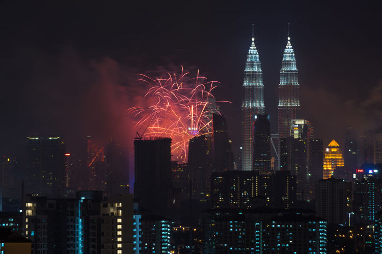 Illuminated petronas towers and fireworks at night