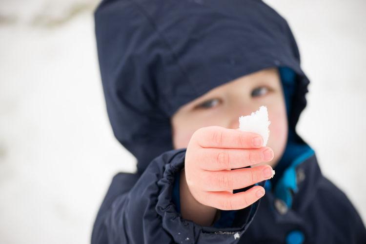 Close-up of boy holding snow