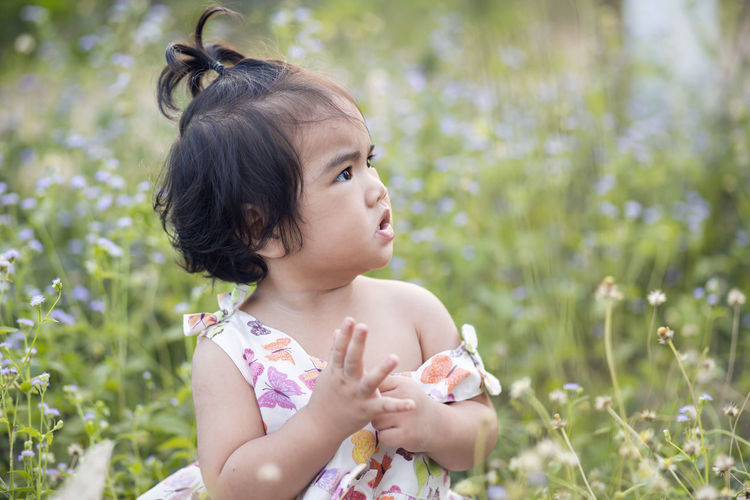 Close-up of girl looking away while standing against plants