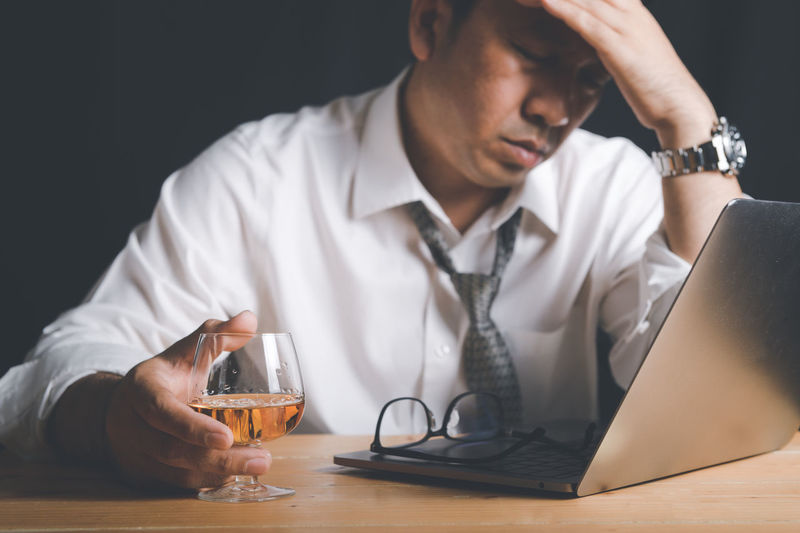 Businessman hold whiskey glass and feel stressed,