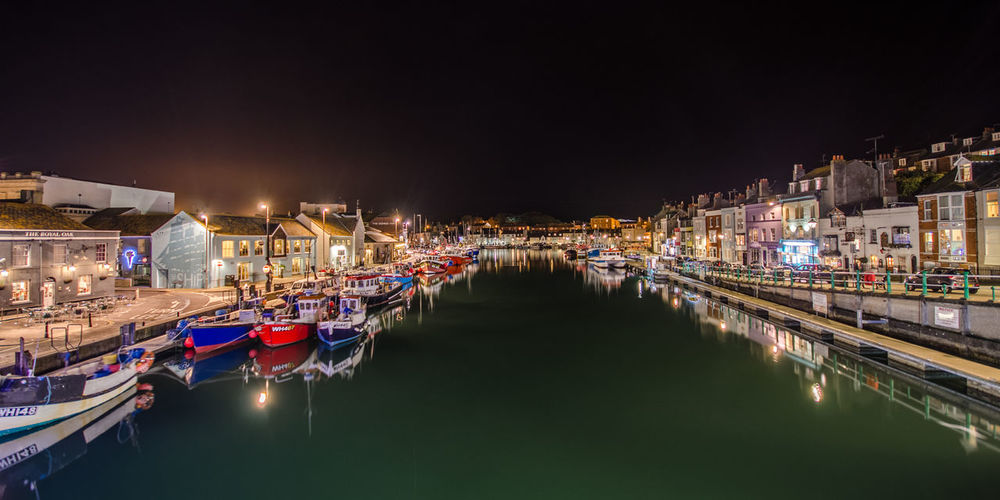 Boats moored at harbor against clear sky at night
