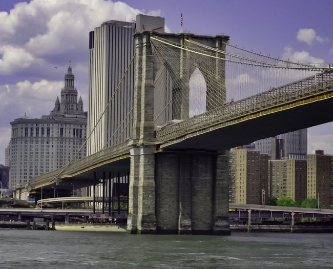 Architecture Built Structure Bridge - Man Made Structure Connection Water Building Exterior Sky River Iconic Brooklyn Bridge / New York Manhattan Municical Building Outdoors Day Low Angle View Travel Destinations Waterfront Cloud - Sky Architectural Column No People Bridge City